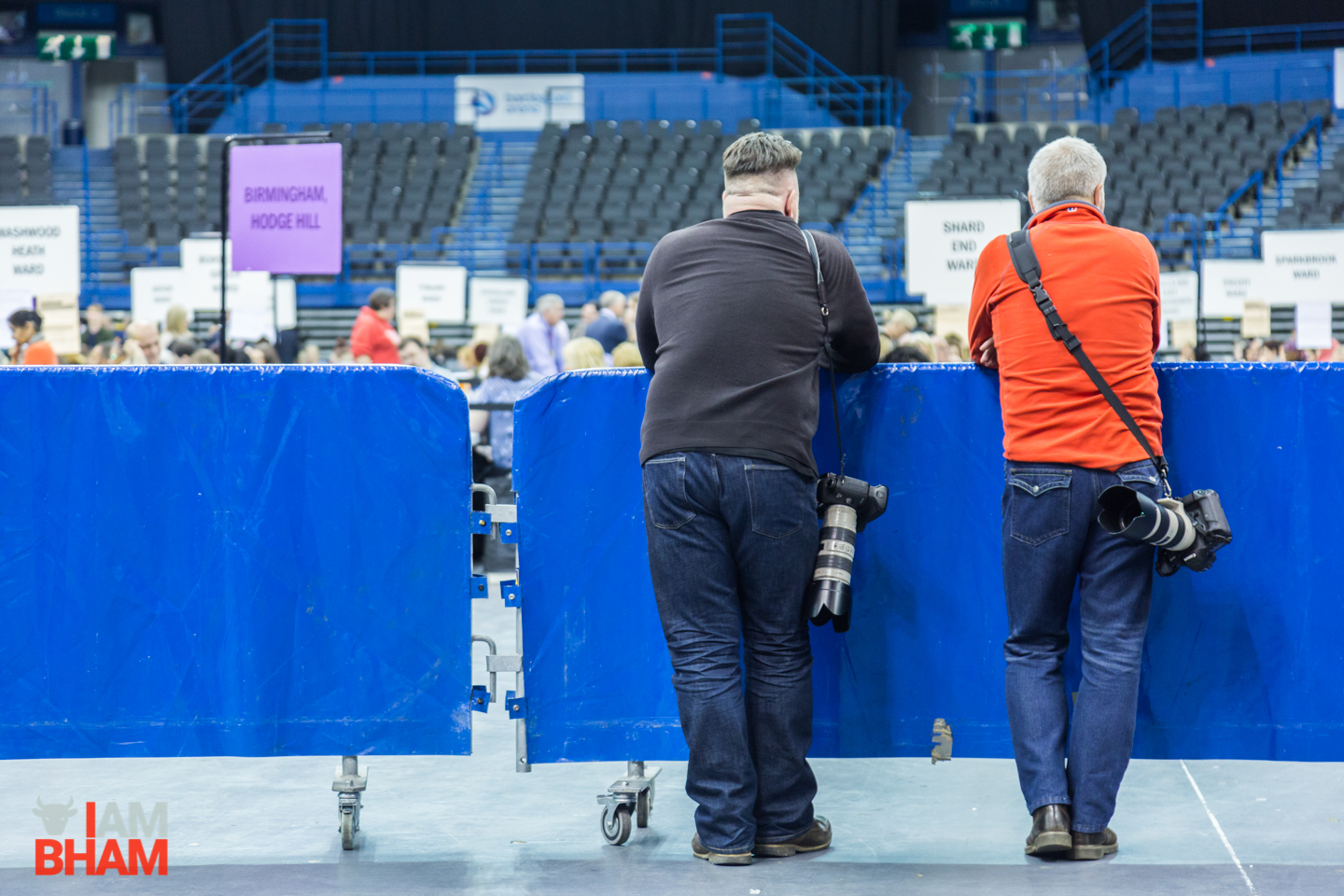 Two men watch the West Midlands Mayoral Election count in Birmingham