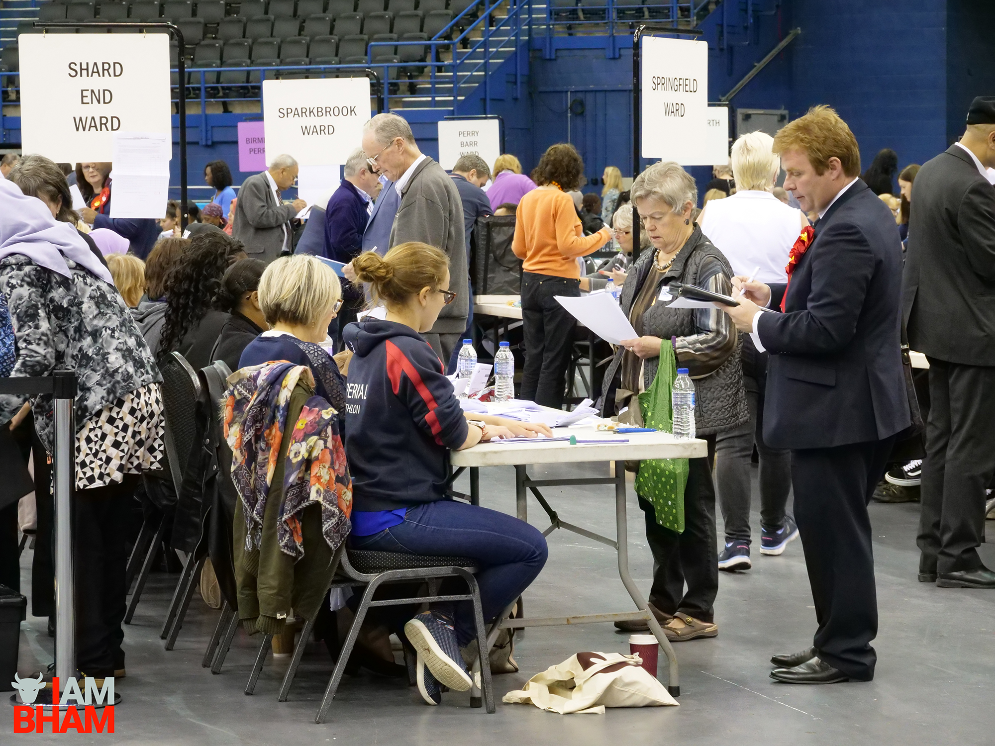 Political party members observe the official West Midlands Mayoral Election vote count at the Birmingham Barclaycard Arena