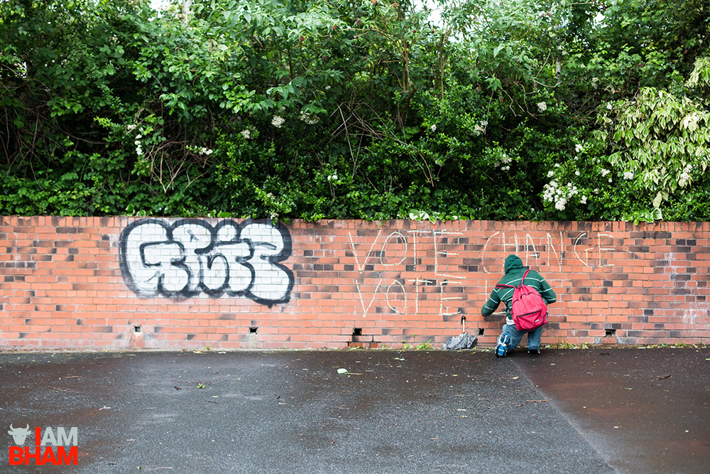 A young street artist writes a political message calling for change, on the eve of the 2017 General Election