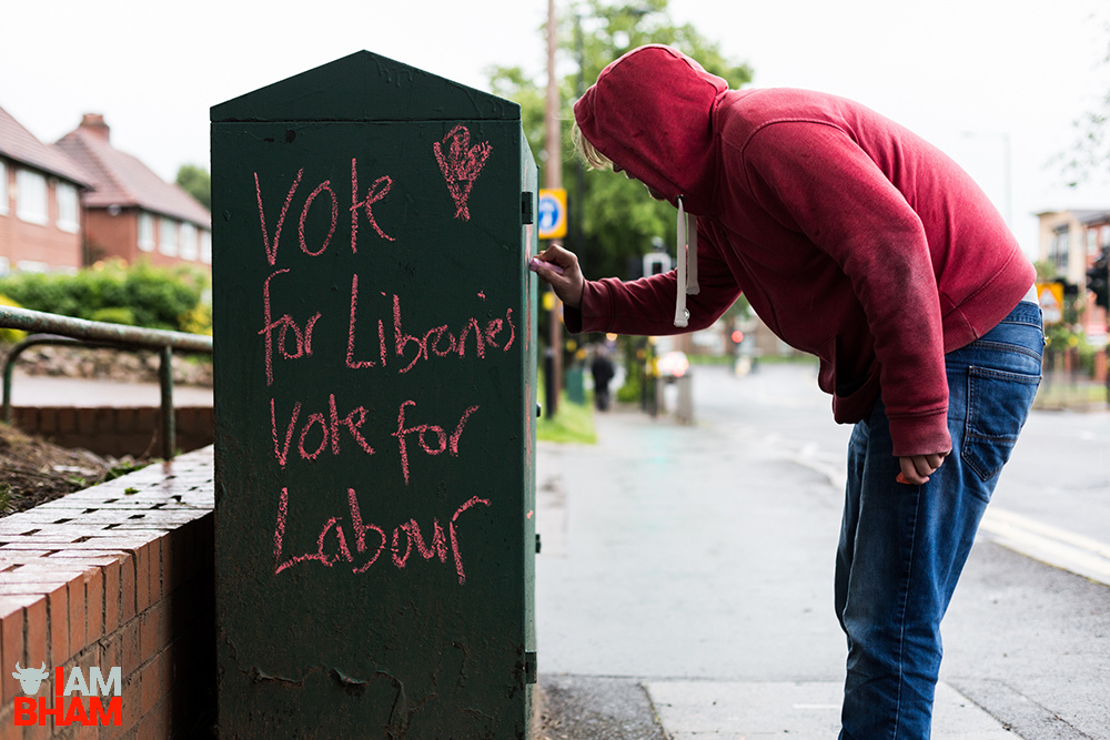 A artist activist leaves the message 'Vote for Libraries, Vote for Labour' in Birmingham