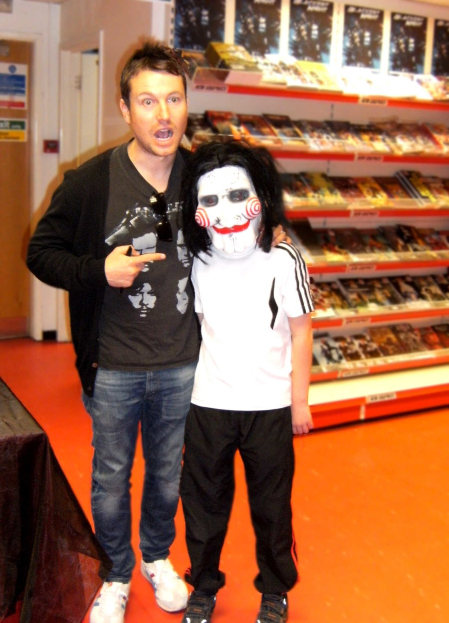 Leigh Whannell pulls a face and poses with a young fan dressed up as Billy the Puppet from the SAW film franchise