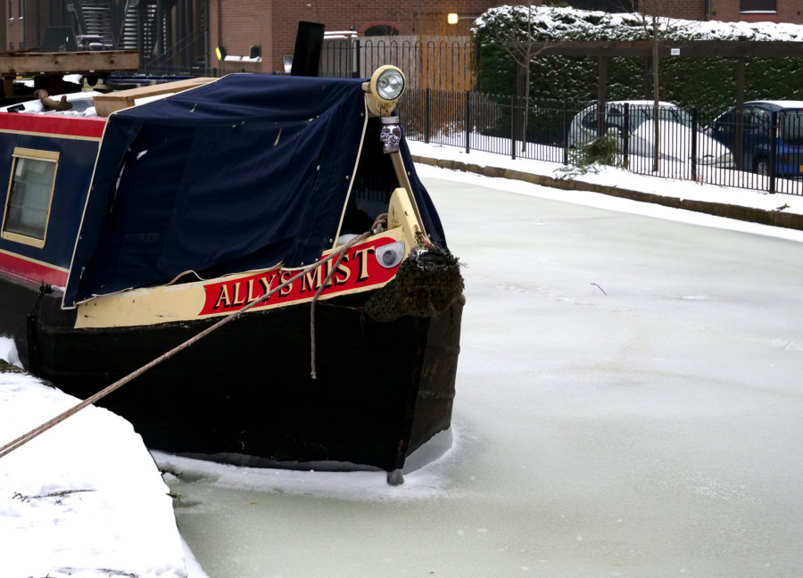 A canal boat anchored in ice in Birmingham