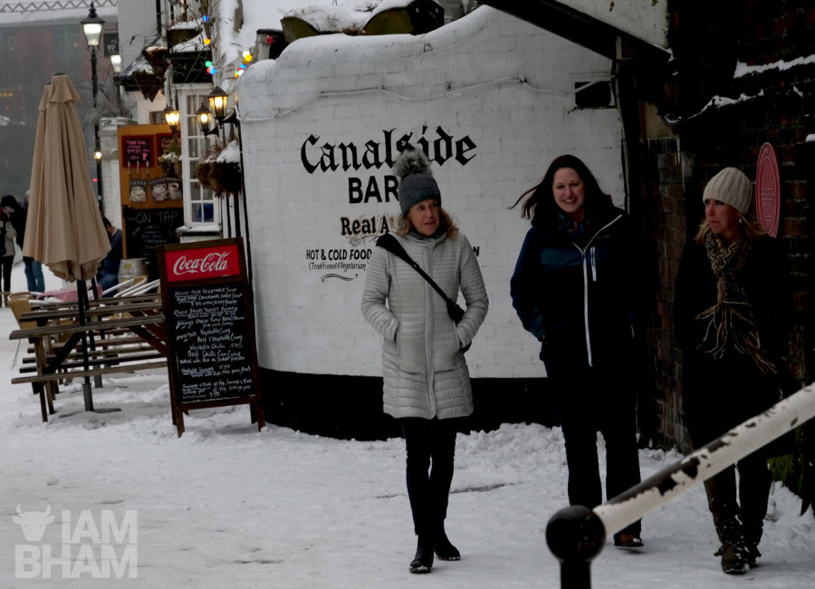 Friends walk alongside frozen canals in Birmingham