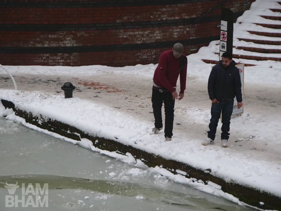 Young lads attempting to break the ice on frozen canals using snow balls