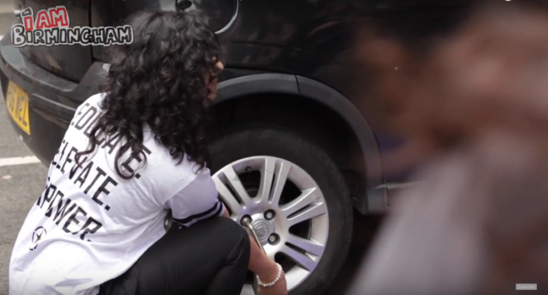 Women teaching other women how to successfully change a tyre at the PMT festival in Birmingham