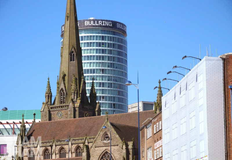 The Rotunda peeking out from behind St. Martin's Church in Birmingham city centre