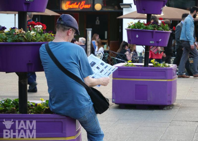 A man reads a magazine in Hurst Street in Birmingham Southside