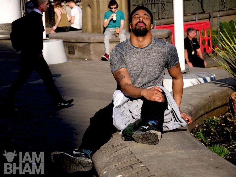 A man soaking in the sun in Birmingham's Victoria Square