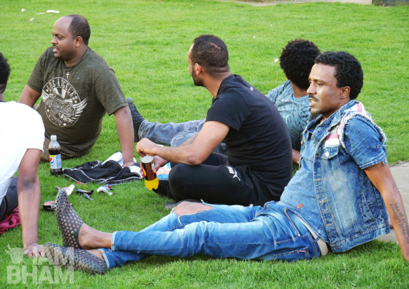 Friends relax on the grass around Birmingham Cathedral