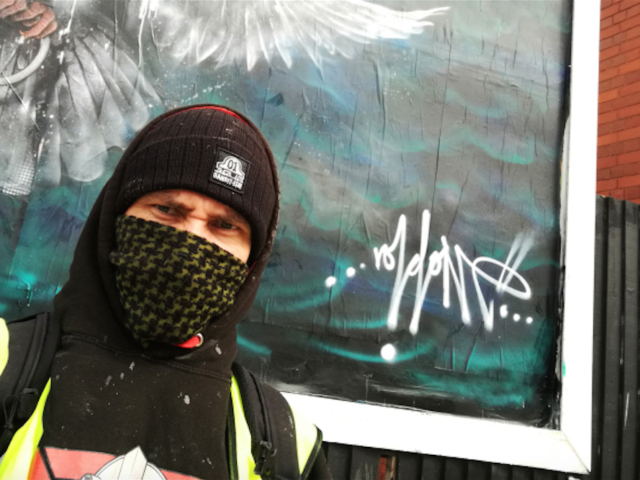 Guerrilla street artist Void One in front of his political anti-war piece