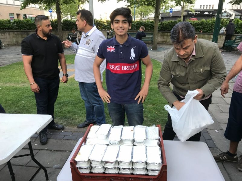 A young volunteer ready to distribute hot food packs to those in need