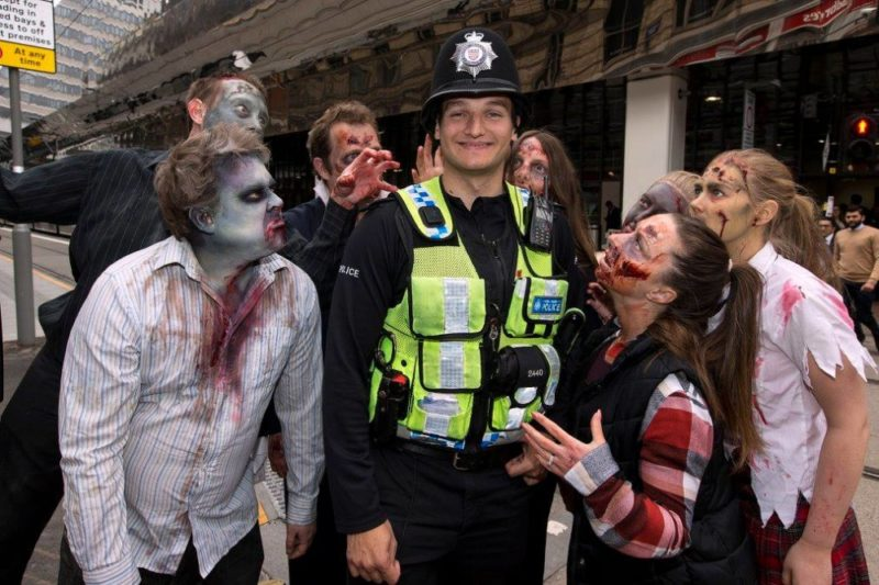 Zombies cosy up to a West Midlands Police officer during a special Midland Metro takeover