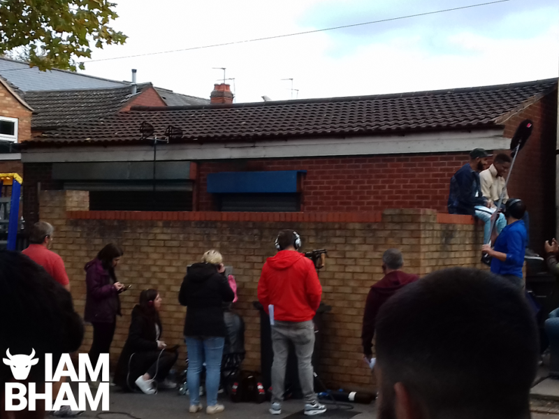 Technicians and engineers hide behind a wall as filming of 'Man Like Mobeen' gets underway
