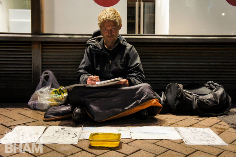 A man sits in New Street in Birmingham city centre