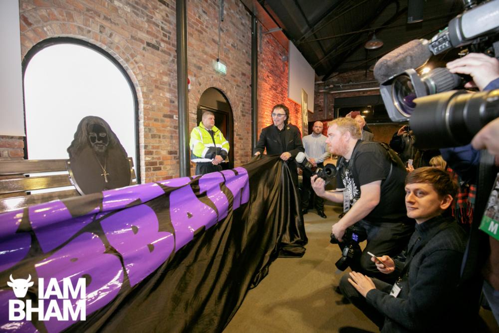 Toni Iommi of Black Sabbath unveils heavy metal bench tribute in Birmingham, as Lyle Bignon watches.
