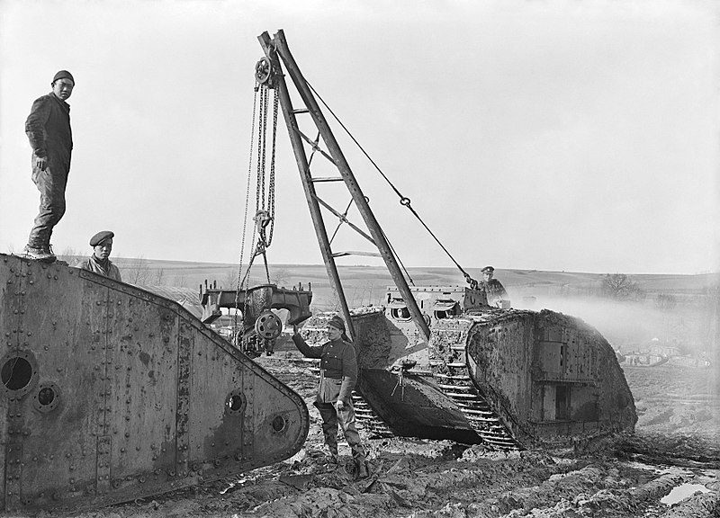The British Army on the Western Front during World War One (1914-1918) with Chinese labourers hoisting parts from a salvaged tank by crane at the Central Stores, Tank Corps. Teneur, spring 1918.