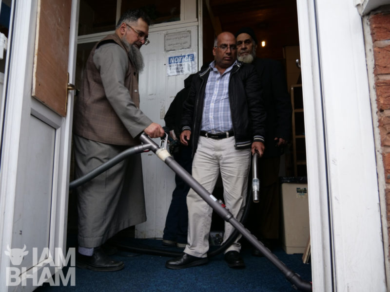 Mosque officials clean up the shattered glass and mess following the attack on the Islamic centre in Witton in Birmingham