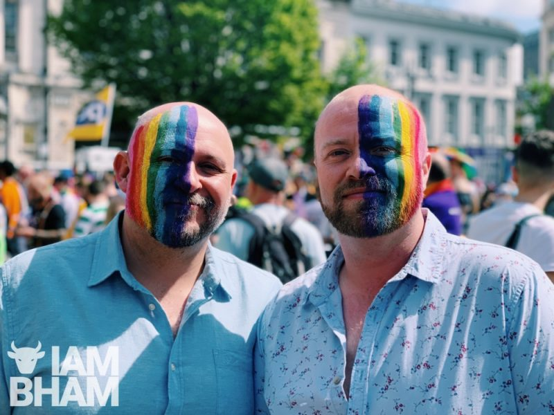 Two Pride goers painted with the iconic Rainbow flag