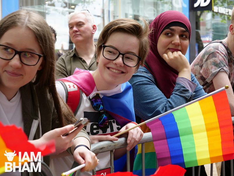 A Muslim woman in hijab watches the Birmingham Pride parade 2019 go past with other LGBT supporters