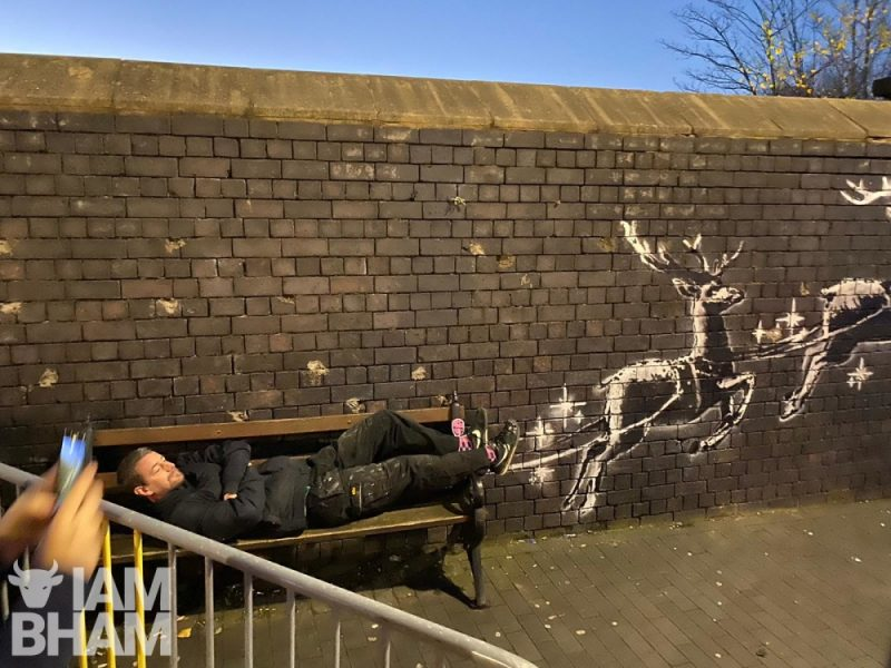 Local Ste welsh poses with the Banksy artwork in the Jewellery Quarter in Birmingham