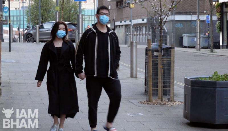 A couple wearing masks walk down John Bright Street in Birmingham city centre