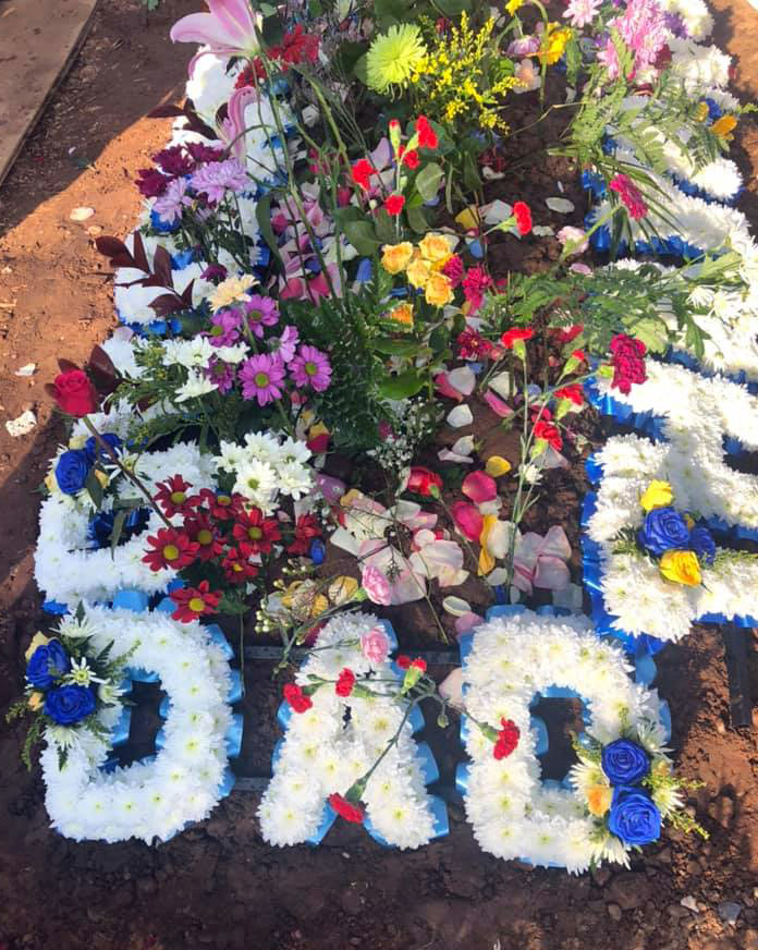 "Flowers spelling out the words ""Dad"" and ""Grandad"" were also placed on Afsar Hussain's graveside"