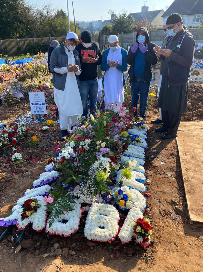 Afsar Hussain's sons wore face masks and sanitary gloves as they prayed over his grave