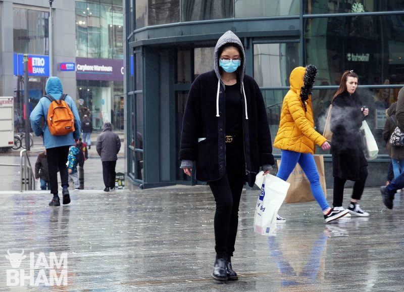 A woman wearing a face mask walks through the Bullring in Birmingham on Wednesday (March 18)