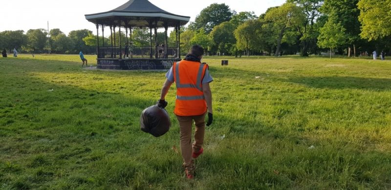A Waste Warrior picks up picnic litter in Small Heath Park