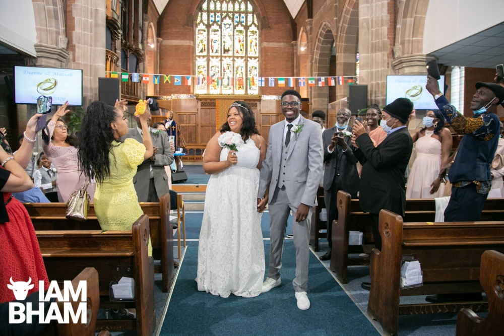 Dionne Brown and Maciah Smith walk down the aisle at the New Testament Church Of God in Highgate, Birmingham