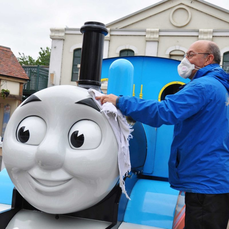A staff member cleaning Drayton Manor Park's Thomas the Tank Engine attraction