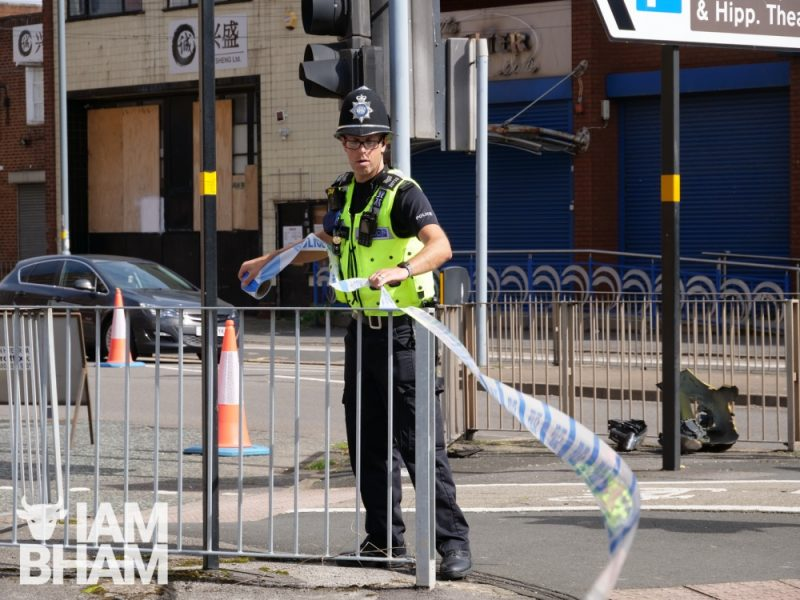 A police officer unfurls police tape to cordon off Hurst Street as part of a crime scene
