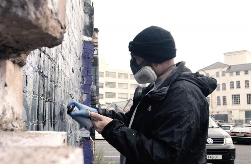 Birmingham-based artist David Brown aka Panda spraying 'The Rap Game' promotional artwork in Digbeth