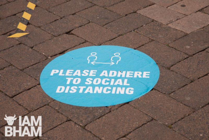 Social distancing street sign pavement Birmingham 2020