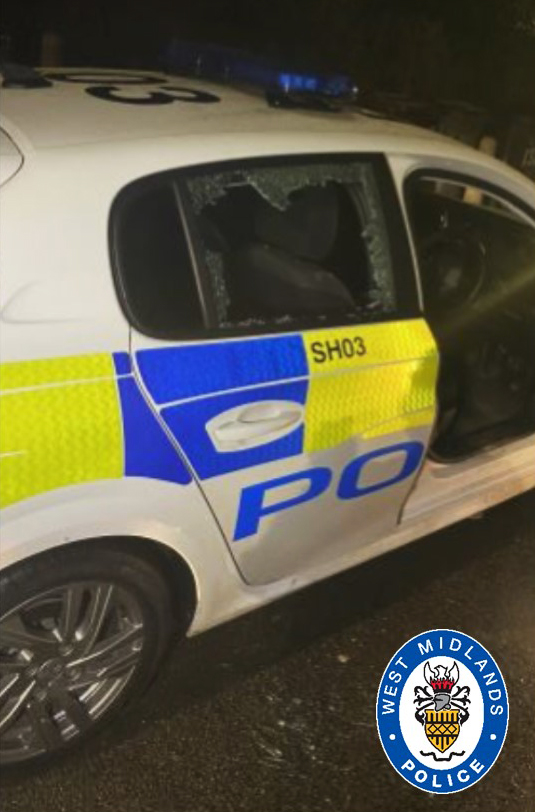 The police car with a smashed window after a brick was thrown at the vehicle