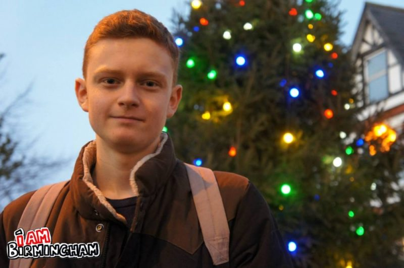 Election candidate Luke Holland stands in front of a Christmas Tree in Moseley Village in Birmingham