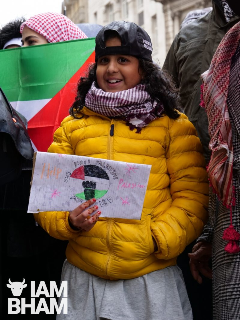 A young girl holds a home-made sign in support of Palestine