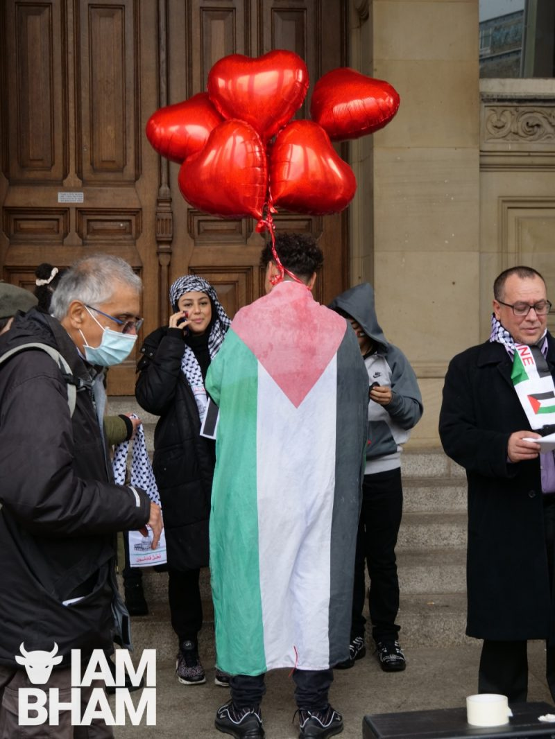 A young man carries heart-shaped balloons while draped with the Palestinian flag