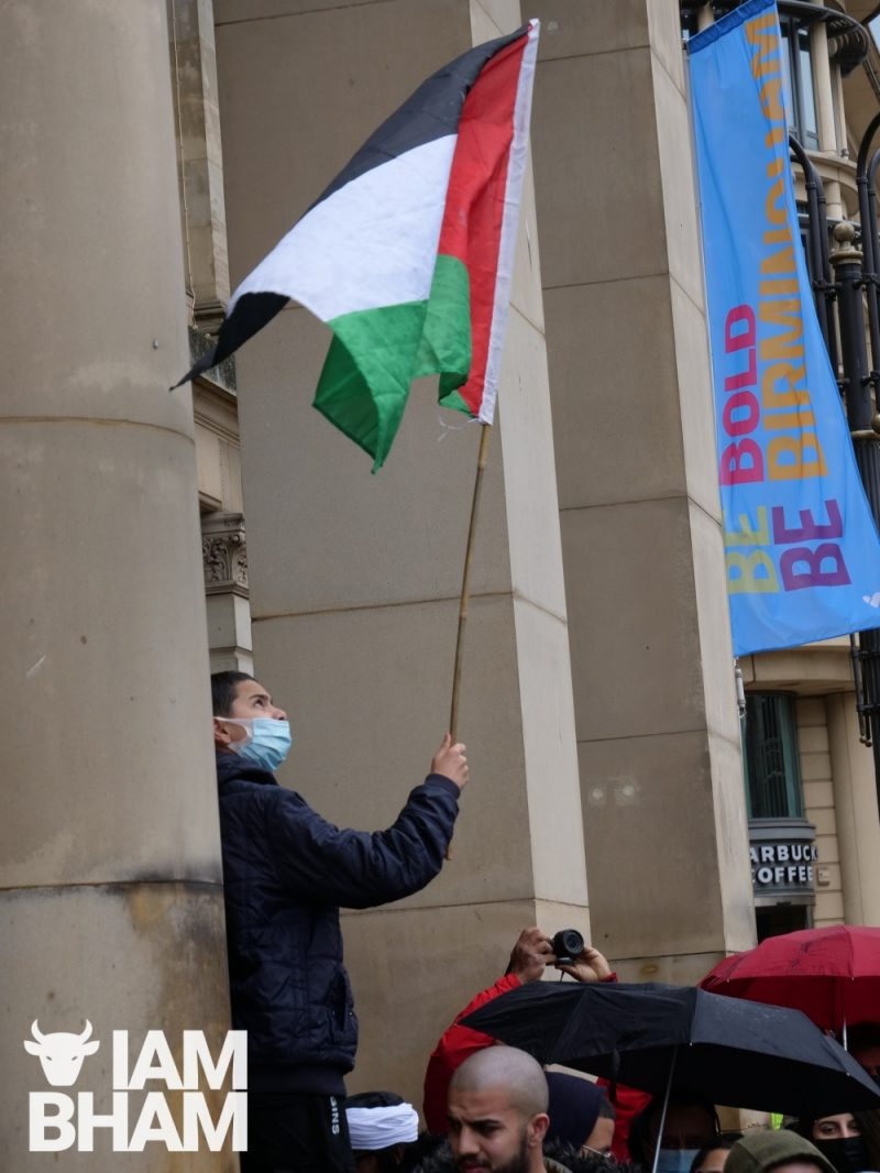 A young boy flies the flag of Palestine at Birmingham City Council House