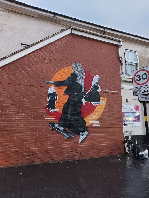The street art depicts a young Muslim girl on a skateboard